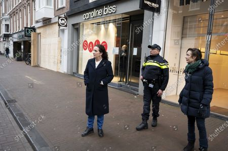 Amsterdam's Mayor Femke Halsema (L) takes a look at he PC Hooftstraat, a street known for its expensive shopping brands, where shopkeepers have barricaded their business in Amsterdam, the Netherlands, 27 January 2021. The entrepreneurs in the chic shopping street fear damage if riots break out. Since the introduction of the curfew, there have been riots in multiple cities across the Netherlands.