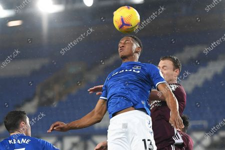 Stock Image of Everton's Yerry Mina, center, jumps for a header with Leicester's Jonny Evans during the English Premier League match between Everton and Leicester City at the Goodison Park stadium in Liverpool, England