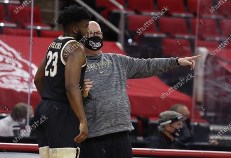 Wake Forest coach Steve Forbes talks with Isaiah Wilkins (23) during the first half of the team's NCAA college basketball game against North Carolina State, in Raleigh, N.C