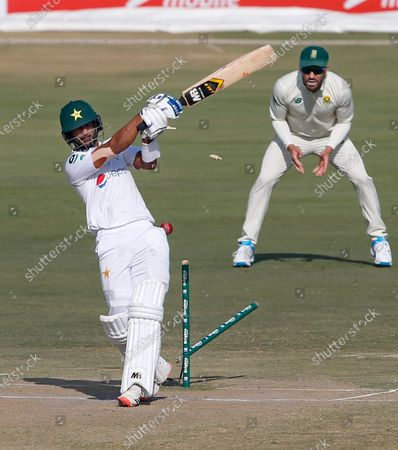 Pakistan's Hasan Ali, front, is bowled by South Africa's Kagiso Rabada as Faf du Plessis watches during the third day of the first cricket test match between Pakistan and South Africa at the National Stadium, in Karachi, Pakistan