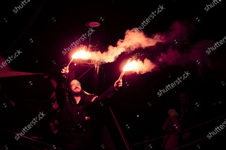 French skipper Louis Burton, 35, who sailed his Imoca 60 monohull 'Bureau Vallee' in the 2020/2021 ninth edition of the Vendee Globe round-the-world solo race, celebrates with flares after crossing the finish line at Les Sables d'Olonne, western France