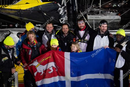 French skipper Louis Burton, 35, who sailed his Imoca 60 monohull 'Bureau Vallee' in the 2020/2021 ninth edition of the Vendee Globe round-the-world solo race, poses with his wife Servane (L), his children and members of staff in front of the Saint-Malo flag after crossing the finish line at Les Sables d'Olonne, western France. - French Charlie Dalin completed the epic race in 80 days, six hours, 15 minutes and 47 seconds. However, Germany's Boris Herrmann (SeaExplorer-Yacht Club de Monaco) and France's Yannick Bestaven (Maitre coq IV) are still in the running for the title.