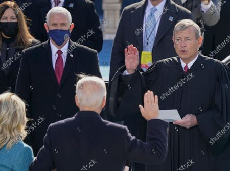 Joe Biden is sworn in as the 46th president of the United States by Chief Justice John Roberts as Jill Biden holds the Bible during the 59th Presidential Inauguration at the U.S. Capitol in Washington, . Former Vice President Mike Pence and Karen Pence are seen upper left