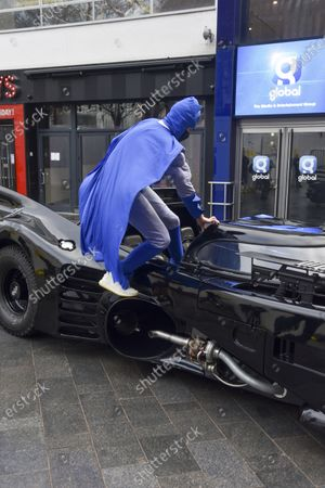 Stock Picture of Capital Breakfast presenter Roman Kemp (L) poses next to his surprise Batmobile ride outside the Capital studios for his 28th birthday. Roman Kemp was gifted a Batmobile as a kid from his godfather George Michael and he still has it. Co-hosts Sonny and Sian are making it a reality for him.
