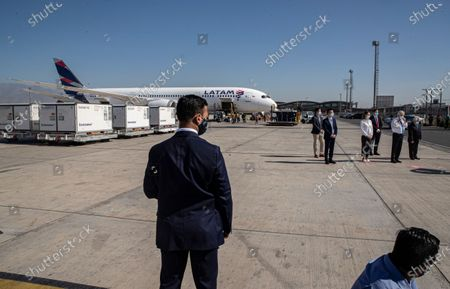 Presidential bodyguard stands near Chilean President Sebastian Pinera, second from far right, during the arrival of the first batch from China of the CoronaVac vaccine for COVID-19, developed by Chinese biopharmaceutical company Sinovac Biotech, at the Arturo Merino airport in Santiago, Chile