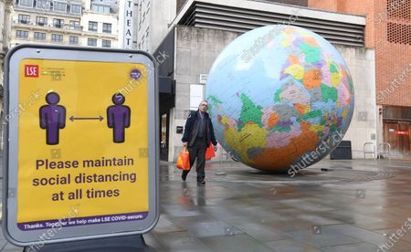 A man walks past an art piece designed by British artist Mark Wallinger is called 'The World turned Upside Down' during third national lockdown in London, Britain, 28 January 2021. A national lockdown across England began on midnight on 05 January 2021. 2020 saw the largest increase in UK deaths in a single year since 1940, according to provisional ONS figures.