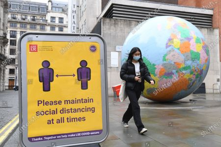 Stock Image of A woman walks past an art piece designed by British artist Mark Wallinger is called 'The World turned Upside Down' during third national lockdown in London, Britain, 28 January 2021. A national lockdown across England began on midnight on 05 January 2021. 2020 saw the largest increase in UK deaths in a single year since 1940, according to provisional ONS figures.
