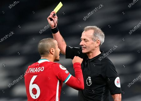 Liverpool's Thiago (L) is shown a yellow card by referee Martin Atkinson (R) during the English Premier League soccer match between Tottenham Hotspur and Liverpool FC in London, Britain, 28 January 2021.