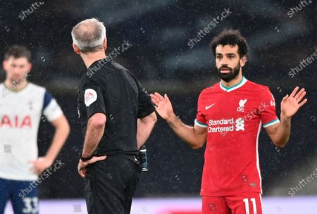 Liverpool's Mohamed Salah (R) talks to referee Martin Atkinson (L) during the English Premier League soccer match between Tottenham Hotspur and Liverpool FC in London, Britain, 28 January 2021.