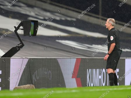 Referee Martin Atkinson checks the VAR decision during the English Premier League soccer match between Tottenham Hotspur and Liverpool FC in London, Britain, 28 January 2021.