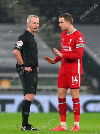 Liverpool's Jordan Henderson (R) talks to referee Martin Atkinson during the English Premier League soccer match between Tottenham Hotspur and Liverpool FC in London, Britain, 28 January 2021.