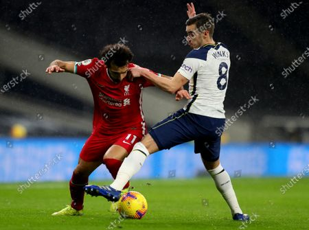 Liverpool's Mohamed Salah, left, and Tottenham's Harry Winks challenge for the ball during the English Premier League soccer match between Tottenham Hotspur and Liverpool at the Tottenham Hotspur Stadium in London