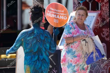 """Bystander looks up to see People for the Ethical Treatment of Animals (PETA) supporter Yari Vivanco, left, as she demonstrates against injustice while painted as a macaw, along Fort Lauderdale Beach Boulevard in Fort Lauderdale, Fla. """"PETA is asking everyone to reject human supremacism,"""" says PETA President Ingrid Newkirk. """"I am an animal. We are all animals. There aren't animals and us. There isn't a human race and all the other races. That's a supremacist idea, and it should be stamped out, just like all other forms of supremacy"""