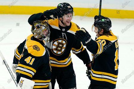 Boston Bruins goaltender Jaroslav Halak (41), defenseman Brandon Carlo (25), and left wing Anders Bjork (10) celebrate their victory over the Pittsburgh Penguins in an NHL hockey game, in Boston