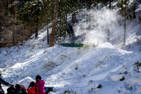 Stock Photo of WRIGHTWOOD, CA - With his family watching, Edgar Gomez, of Inglewood, soars off a makeshift snow jump thanks to snow from recent storms and more is forecasted to arrive in the San Gabriel Mountains near Wrightwood Wednesday, Jan. 27, 2021. (Allen J. Schaben / Los Angeles Times)