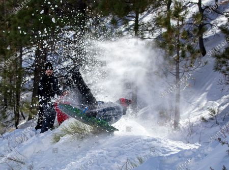WRIGHTWOOD, CA - With his family watching, Edgar Gomez, of Inglewood, soars off a makeshift snow jump thanks to snow from recent storms and more is forecasted to arrive in the San Gabriel Mountains near Wrightwood Wednesday, Jan. 27, 2021. (Allen J. Schaben / Los Angeles Times)