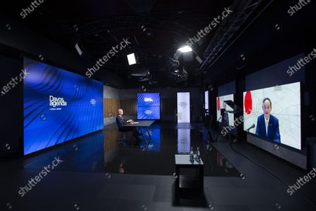 Klaus Schwab (L), Founder and Executive Chairman of the World Economic Forum (WEF), listens to Japanese Prime Minister Yoshihide Suga displayed on screens during a video conference at the Davos Agenda, in Cologny near Geneva, Switzerland, 29 January 2021. The Davos Agenda runs from 25 to 29 January 2021 as an online edition due to the coronavirus COVID-19 pandemic.