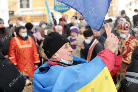 An aged man wrapped in a Ukrainian flag takes a photo during a march towards Askold's Grave Park on the Kruty Heroes Remembrance Day, Kyiv, capital of Ukraine. On this day, the country pays tribute to almost 400 soldiers of the Ukrainian People's Republic, mostly students, who sacrificed their lives to stop the advance of the Bolshevik Red Army forces of about 4,000 men commanded by Mikhail Muravyov near the Kruty railway station, 130 kilometres north-east of Kyiv, on January 29, 1918.