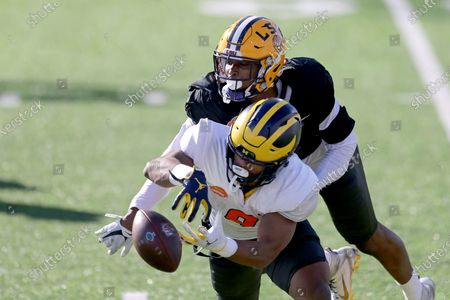 Running back Chris Evans of Michigan (9) has the ball batted away by defensive back JaCoby Stevens of LSU (7) during the American team practice for the NCAA college football Senior Bowl in Mobile, Ala