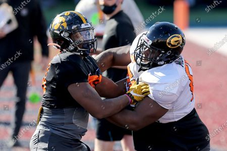 Defensive lineman Chauncey Golston of Iowa (90) and offensive lineman David Moore of Grambling State (FCS) (60) participate in a blocking drill during the American team practice for the NCAA college football Senior Bowl in Mobile, Ala
