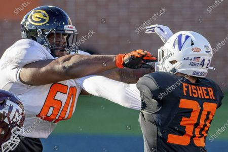 American Team offensive lineman David Moore of Grambling State (FCS) (60) blocks American Team linebacker Paddy Fisher of Northwestern (30) during the American Team practice for the NCAA Senior Bowl college football game in Mobile, Ala