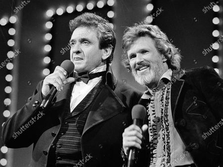 """Country stars Johnny Cash, left and Kris Kristofferson sing during the Country Music Awards in Nashville, Tenn., Oct. 1983. Kristofferson has retired after five decades. A statement from his publicist said the Country Music Hall of Famer and Grammy winner retired in 2020. His son, John, stepped in last year to oversee his father's business including his record label. The Texas-born Oxford scholar brought introspective and poetic lyrics to country music with songs like """"Sunday Mornin' Comin' Down"""" and """"Me and Bobby McGee."""" He was a member of the supergroup The Highwaymen and starred in 70 films over his career"""