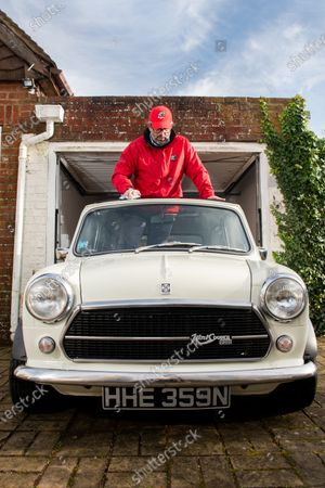 Stock Picture of Freddie St George MBE, co-founder of the annual road trip event 'The Italian Job' where he and hundreds of other Mini Cooper fanatics undertake a 10-day road trip to Italy whilst raising money for charity, polishes his 1974 Innocenti Mini Cooper through his sun roof at his home in Hove, East Sussex as the race has been cancelled for the second consecutive year.  Freddie was recently awarded an MBE for his services to charity after raising just shy of £3 million for local charities since the races inception in 1990, which the race was cancelled for the first time in its 30 year history last year due to the coronavirus pandemic.   However Freddie is hoping to undertake a localised adaption of the race, 'Mile of Minis' later this year starting in Oxford and finishing in Windsor, raising funds for Buttle UK, lockdown regulations permitting.