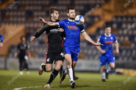 Stock Image of Colchester United's Thomas Smith (5) controls the ball challenged by John McAtee (45) of Scunthorpe United during the EFL Sky Bet League 2 match between Colchester United and Scunthorpe United at the JobServe Community Stadium, Colchester