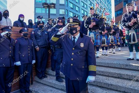 """Jersey City Police Chief Michael Kelly, center, salutes his police officers as he exits police headquarters during his """"walk out"""" ceremony in honor of his retirement, in Jersey City, N.J. Kelly joined the JCPD in 1988, rising through the ranks to become the leader of the department in 2018"""