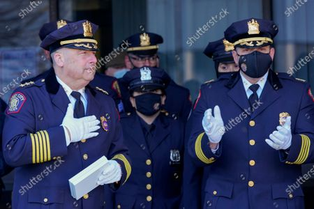 """Jersey City Police Chief Michael Kelly, left, places his hand on his heart after receiving the keys to the city during his """"walk out"""" ceremony in honor of his retirement, in Jersey City, N.J. Kelly joined the JCPD in 1988, rising through the ranks to become the leader of the department in 2018"""