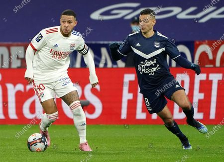 Lyon's Memphis Depay, left, and Bordeaux's Hatem Ben Arfa battle for the ball during the French League One soccer match between Lyon and Bordeaux in Lyon, France