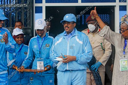 Somalia's President Mohamed Abdullahi Mohamed, center, prepares to cut the ribbon for the reopening of the stadium in Mogadishu, Somalia. As Somalia marks three decades since a dictator fell and chaos engulfed the country, the government is set to hold a troubled national election but two regional states are refusing to take part in the vote to elect Somalia's president and time is running out before the Feb. 8 date on which mandates expire