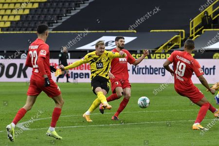 Dortmund's Julian Brandt, second left, attempts a shot at goal in front of Augsburg's Felix Uduokhai during the German Bundesliga soccer match between Borussia Dortmund and FC Augsburg in Dortmund, Germany