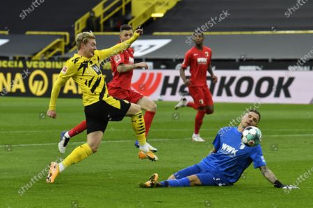 Dortmund's Julian Brandt, left, attempts a shot at goal in front of Augsburg's goalkeeper Rafal Gikiewicz during the German Bundesliga soccer match between Borussia Dortmund and FC Augsburg in Dortmund, Germany