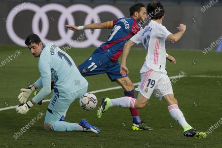 Real Madrid's goalkeeper Thibaut Courtois, left, and Real Madrid's Alvaro Odriozola, right, stop Levante's Jose Luis Morales during the Spanish La Liga soccer match between Real Madrid and Levante at the Alfredo Di Stefano stadium in Madrid, Spain