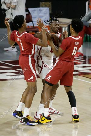 Oklahoma's Victor Iwuakor (0) fights for the ball with Alabama's Herbert Jones (1) and Joshua Primo (11) during the first half of an NCAA college basketball game in Norman, Okla