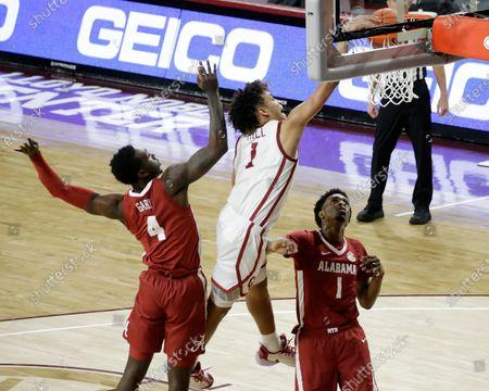 Oklahoma's Jalen Hill (1) dunks the ball against Alabama's Juwan Gary (4) and Herbert Jones (1) during the second half of an NCAA college basketball game in Norman, Okla