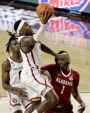 Oklahoma's De'Vion Harmon (11) takes a shot against Alabama's Herbert Jones (1) as Oklahoma's Victor Iwuakor (0) looks on during the second half of an NCAA college basketball game in Norman, Okla