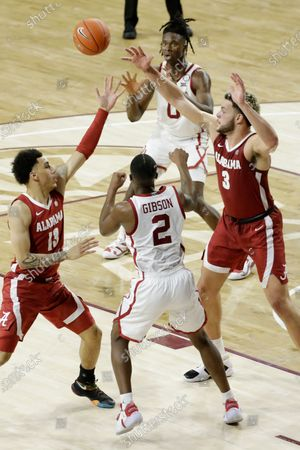 Stock Photo of Oklahoma's Umoja Gibson (2) passes the ball to Victor Iwuakor (0) away from Alabama's Jahvon Quinerly (13) and Alex Reese (3) during the second half of an NCAA college basketball game in Norman, Okla