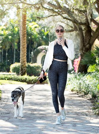 Kate Upton stays sporty in an Old Navy Powersoft Active set on while on a walk with her dog.