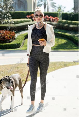 Stock Picture of Kate Upton stays sporty in an Old Navy Powersoft Active set on while on a walk with her dog.