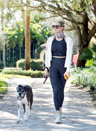 Stock Image of Kate Upton stays sporty in an Old Navy Powersoft Active set on while on a walk with her dog.
