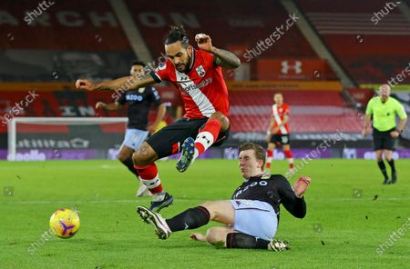 Southampton's Theo Walcott jumps over a challenge by Aston Villa's Matt Targett during the English Premier League soccer match between Southampton and Aston Villa at St. Mary's Stadium in Southampton, England