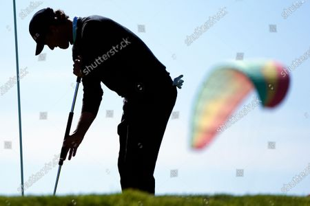 Adam Scott, of Australia, putts on the 12th hole of the South Course as a paraglider passes in the background during the third round of the Farmers Insurance Open golf tournament at Torrey Pines, in San Diego