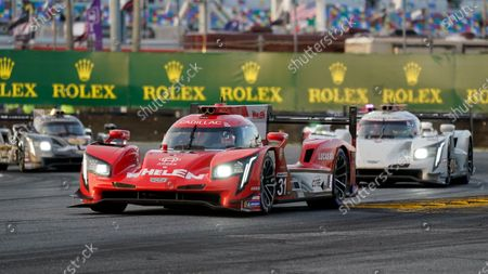 Felipe Nasr of Brazil (31) leads Renger van der Zande, right, of the Netherlands, Loic Duval, left, of France though the horseshoe turn during the Rolex 24 hour auto race at Daytona International Speedway, in Daytona Beach, Fla