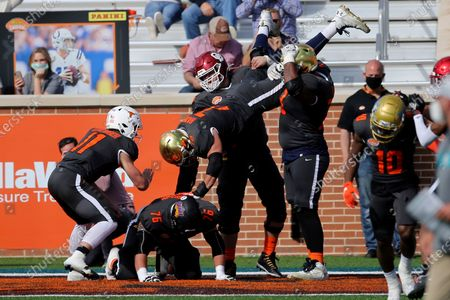 National Team quarterback Sam Ehlinger of Texas (11), offensive lineman Spencer Brown of Northern Iowa (76), offensive lineman Robert Hainsey of Notre Dame (72), offensive lineman Creed Humphrey of Oklahoma (56), and offensive lineman Aaron Banks of Notre Dame (73), celebrate a touchdown during the first half of the NCAA college football Senior Bowl in Mobile, Ala