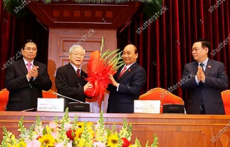 Vietnam Communist party General Secretary Nguyen Phu Trong, center left, is presented with a bouquet by Prime Minister Nguyen Xuan Phuc, center right, in Hanoi, Vietnam, . Vietnam Communist Party has re-elected Nguyen Phu Trong for another term as the party's General Secretary, the country de-facto top leader