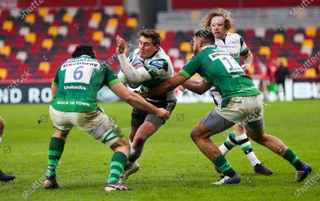 Toby Flood (co-captain) of Newcastle tackled by Curtis Rona of London Irish & Matt Rogerson  (Captain) of London Irish