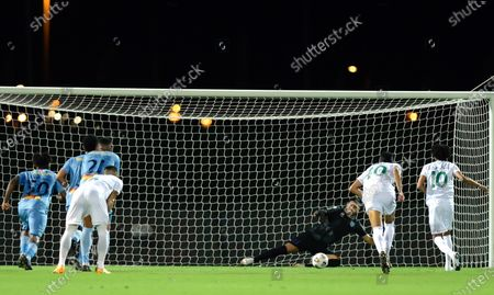 Al-Ahli's player Salman Al-Muwashar (R) scores a penalty kick against Al-Batin's goalkeeper Martin Campana (3-R) during the Saudi Professional League soccer match between Al-Ahli and Al-Batin at King Abdullah Sport City Stadium, 30 kilometers north of Jeddah, Saudi Arabia, 31 January 2021.