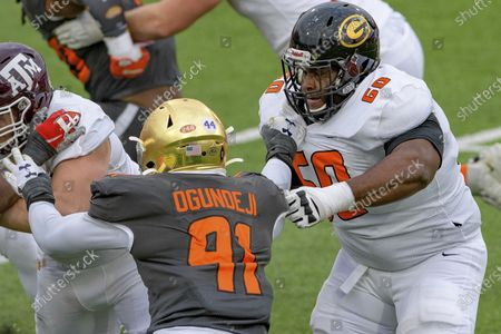 American Team offensive lineman David Moore of Grambling State (FCS) (60) battles National Team defensive lineman Adetokunbo Ogundeji of Notre Dame (91) during the NCAA Senior Bowl college football game in Mobile, Ala